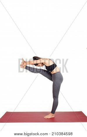 young asian woman doing yoga in Utthita Hasta Padangusthasana yoga pose on the mat isolated on white background exercise fitness sport training healthy lifestyle and people concept