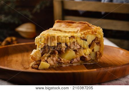 Piece Of Chicken Meat Pie With Potatoes, Apples And Chanterelles On A Wooden Plate