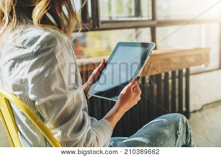 Sunny day. Close-up of tablet computer in hands of young woman sitting in room on chair.Hipster girl working online, blogging, chatting, checking email, watching video blog. Online marketing, education.