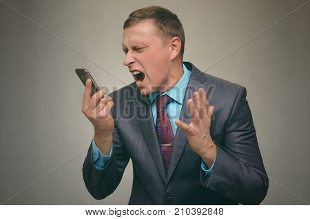 Angry business man in suit scream talking on mobile phone isolated. Stress conversation. Stressful situation.