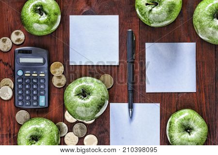 The Concept: Business, Investment, Enrichment. Green Apples, Gold Coins, Calculator And Paper For En