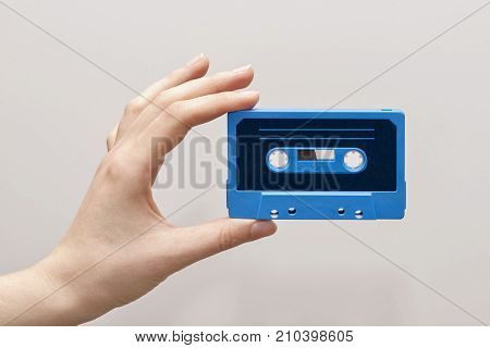 hand holding blue cassette tape isolated in white background