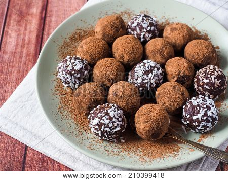 Homemade chocolate truffles with cocoa and coconut on the plate,