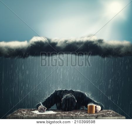 Depressive business man trying to work. Business man with a cloud above his office with heavy rain.