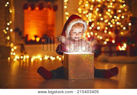 Merry Christmas!happy baby boy with magic gift at home near Christmas tree and fireplace