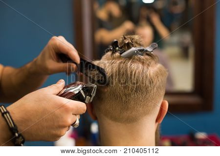 Barber beard with trimmer at barbershop, closeup of client's head. Male Barbershop