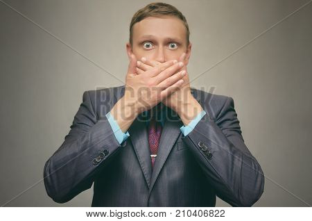 Young man in a suit covers his mouth with his hands. Speak no evil.