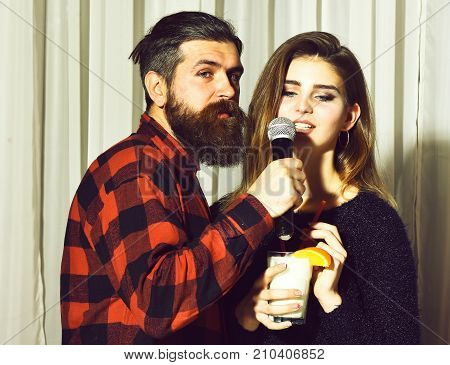 Pretty girl or beautiful woman with cocktail in glass and bearded man hipster with beard in red plaid shirt singing to microphone at karaoke bar party on white curtain
