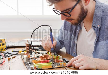 Repairman soldering computer circuit in workshop. Young engineer fixing electronic component of motherboard, copy space