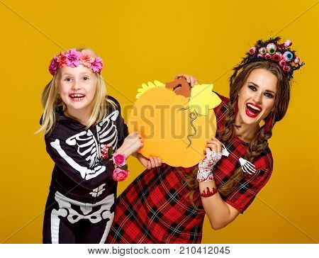 Happy Mother And Child On Yellow Background Showing Pumpkin