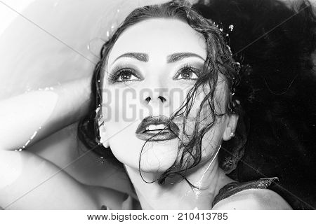 Closeup portrait of one sexual young sensory passionate attractive brunette woman with wet long curly hair and bright makeup lying in bath tab full of water taking shower in cloth horizontal picture