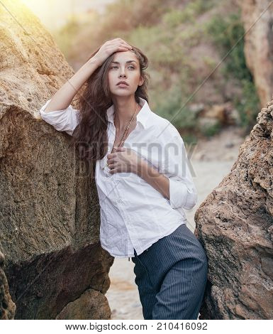 Business Woman On Suit And White Shirt Standing Near Big Stone On The Sea Cost