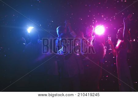 Happy friends celebrating new year at night club. Classy people enjoying life, dancing, drinking champagne and having fun at dark smoky background, showered with confetti. Christmas party background poster