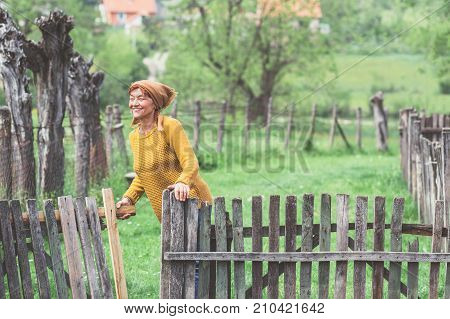 Peasant mature woman in yard, spring at countryside