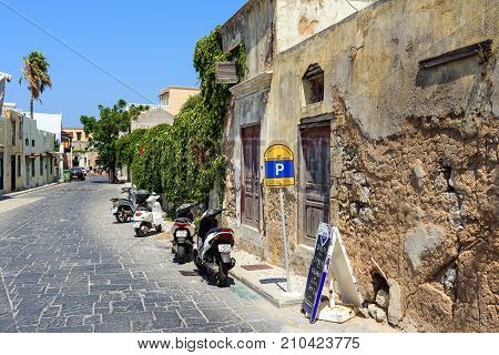 RHODES, GREECE - AUGUST 2017: Motorbike parked at narrow street near Greek cafe in Rhodes town on Rhodes island, Greece