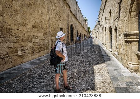 Tourist with rucksack on his back is walking along the narrow street of Rhodes town. Rhodes island, Greece