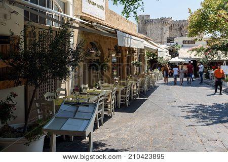 RHODES, GREECE - AUGUST 2017: Street with traditional Greek taverns in Rhodes town. Rhodes island, Greece.