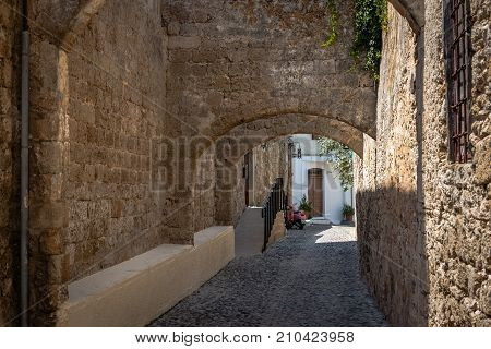 Narrow street with old medieval arches in Rhodes tow. Rhodes island, Greece