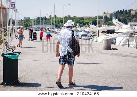 RHODES, GREECE - AUGUST 2017: Tourist with rucksack on his back is walking along the promenade at sea port of Rhodes town. Rhodes island, Greece