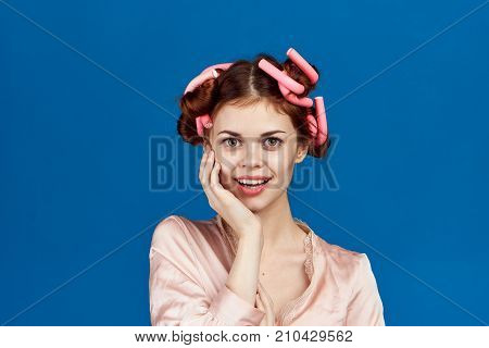 beautiful housewife in curlers on a blue background.