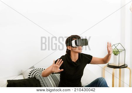 Virtual reality today. Young woman in the world of virtual reality. Smartphone using with VR glasses.