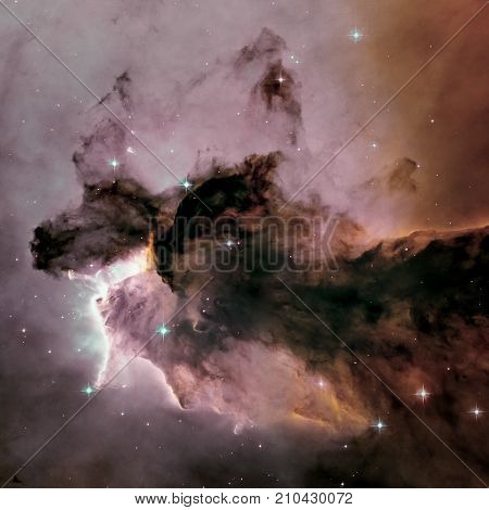 A billowing tower of gas and dust rises from the stellar nursery known as the Eagle Nebula. Space with stars, nebula and galaxy. Image with small DOF. Elements of this image furnished by NASA.
