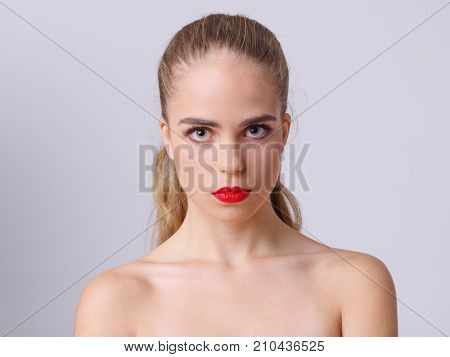 Pretty young girl posing on the camera in studio. Beautiful woman with red lips on a gray background. Close-up of girl. Beauty concept.