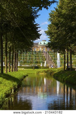 POTSDAM GERMANY - AUG 8 2016: View on the Sanssouci Palace and its staircase from one of the small channel alleys in the park