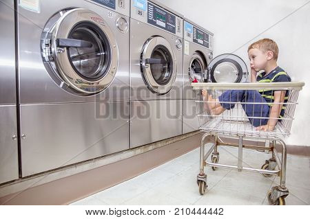 Bored boy in the public laundry. child  sitting in the laundry basket and waiting for the end of washing laundry. The housekeeping concept