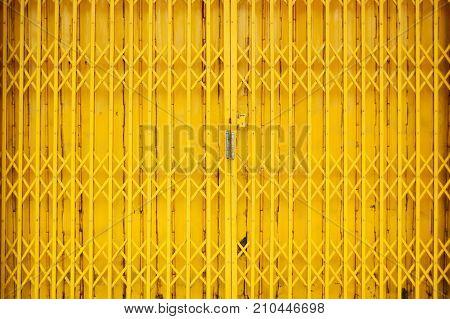 yellow steel door stretch vintage style of close steel door.old style exterior folding gate. ancient metal door texture background Colorful charming attractive door pattern tropical house door style