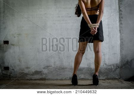 Woman tied with rope sexual robber concept bandit sexual abuse or female hostage in abandoned house copy space the left.