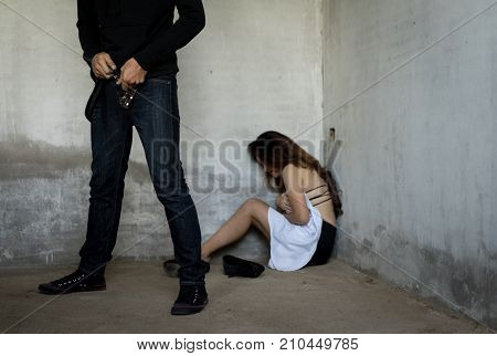 Sexual woman raped and crying concept. Bandit robber zipper of belt jeans in abandoned house closeup