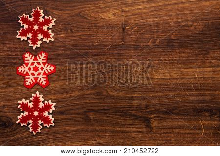Christmas background with three snowflakes on wooden texture