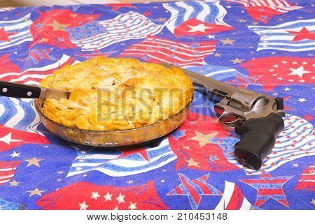 Apple pie sitting on an American flag motif with a gun, total Americana concept