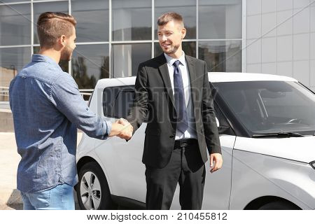 Customer and salesman shaking hands near new car outdoors