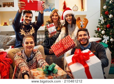 family, Christmas, holidays, happiness and people concept- happy friends sharing Christmas gifts