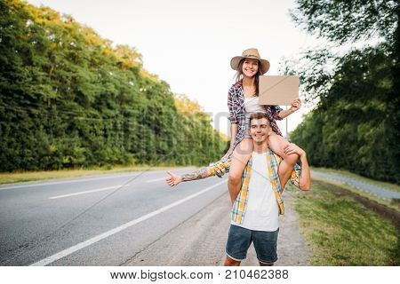 Young hitchhiking couple with empty cardboard
