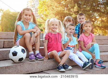 Cute little children with ball sitting on stairs in city park