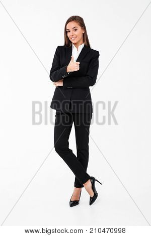 Image of pretty cheerful business woman standing isolated over white background showing thumbs up. Looking camera.