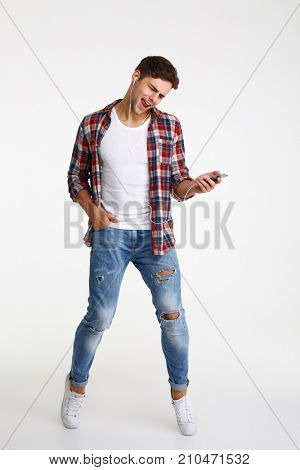 Full length portrait of a joyful young man listening to music with earphones and mobile phone isolated over white background
