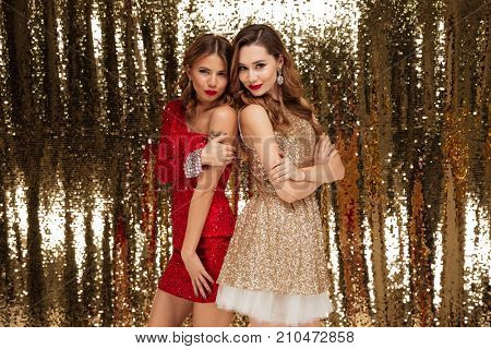 Full length portrait of two lovely pretty women in sparkly dresses standing back to back and looking at camera while standing and posing isolated over golden shiny background