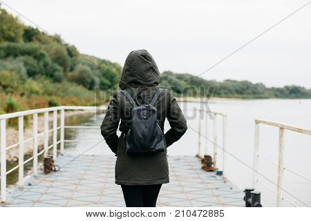 Young woman with backpack walking near the river in autumn season. Girl standing on pier