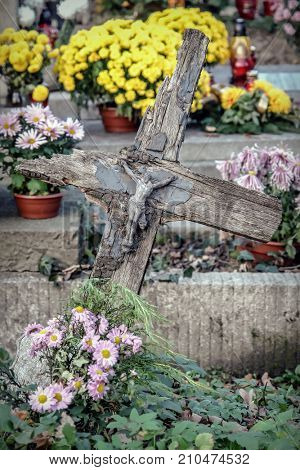 Old forgotten grave with ratty and weathered wooden cross