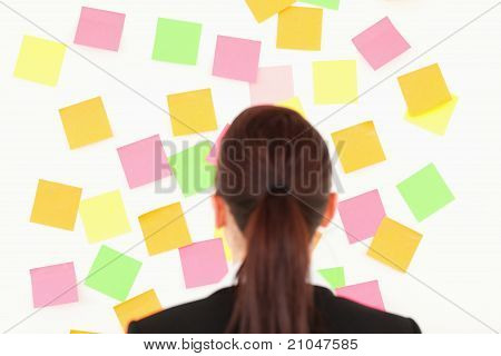 Red-haired Woman Looking At A Wall Full Of Repositional Notes