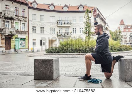 Millenial slim man streching his body in a city site. After-training routine. poster