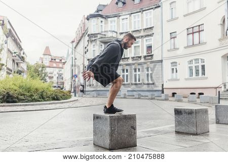 A fit young man, having endurance training in a outdoor urban space. Cardio workout.