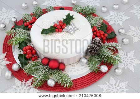 Iced christmas cake with holly, fir, red bauble and white snowflake decorations with silver foil wrapped chocolates on glitter background.
