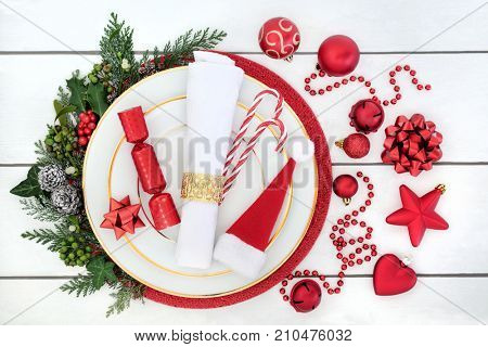 Christmas dinner table setting with porcelain plates, serviette, red decorations with holly, mistletoe, ivy and fir on rustic white wood background