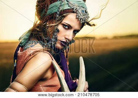 Magnificent gypsy fortune teller with a skull in the rays of the sunset.