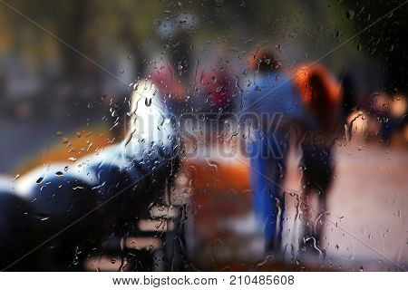 vague silhouette of two people through rainy glass
